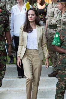 """Als Ehrenbotschafterin des UN-Flüchtlingswerk """"UNHCR"""" reiste Angelina Jolie nach Nairobi, um dort auf das Schicksal von jungen Frauen und Mädchen aufmerksam zu machen. Anmutig tritt sie in einem beigen Hosenanzug durch Menge, auf dem Weg zum Rednerpult."""
