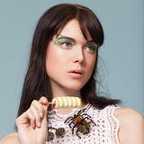 TWISTER-LINER In feinen, kunstvollen Spiralen windet sich der waldmeistergrüne Lidstrich bis in die Augenbrauen. Wer über eine sehr ruhige Hand verfügt, bekommt die Loops mit Flüssigliner gut hin. Alle anderen greifen zur robusteren Kajalstift-Variante. Dann unbedingt darauf achten, dass die Textur wirklich wischfest ist. Broschen von Marni und Gucci über matchesfashion.com, Kleid von Iro