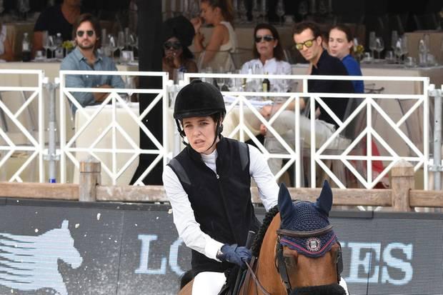 """24. Juni 2017  Charlotte Casiraghi reitet beim """"12. International Monte Carlo Jumping""""-Reitturnier in Cannes, ihr Freund Dimitri Rassam (blaues Hemd, Sonnenbrille) schaut von der Tribüne aus zu."""