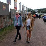 """Poppy Delevingne und Sienna Miller schlendern total entspannt über das Festivalgelände. Dazu passt auch ihr lässiger Look samt Gummistiefeln von Sorel. Während Poppy auf die hohe Variante, die """"Joan Rain Wedges"""", setzt, mag es Sienna flach und wählt die """"Out N'Abouts""""."""