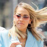 Als Rahmen glitzern an der rotglasigen Sonnenbrille von Rita Ora viele kleine Strasssteinchen.
