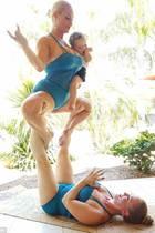 """Coco Austin begeistert mit einer hoch komplizierten Yogapose. """"Göttin"""" wird die Pose genannt und scheint auch ganz gut mit Kind in Arm zu klappen. Cocos Yogalehrerin, die sie gerade mit den Beinen in die Höhe stemmt, ist ihre Schwester Kristy Austin."""