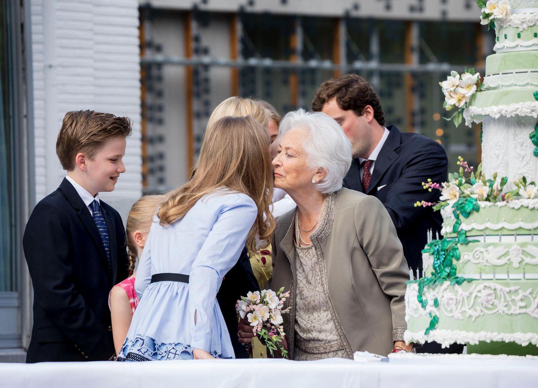 Bei der Übergabe des XXL-Kuchens haben sich alle um Königin Paola versammelt. Alle sind gut gelaunt und weichen nicht von der Seite des Familienoberhaupts. Prinzessin Elisabeth tuschelt mit ihrer Oma, kurz bevor sich alle Blicke auf ein anderen Gast richten.