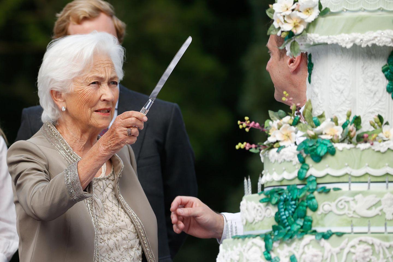 """""""Wo setze ich mit dem Messer bloß an?"""", scheint sich Königin Paola beim Anblick der Riesentorte zu fragen."""