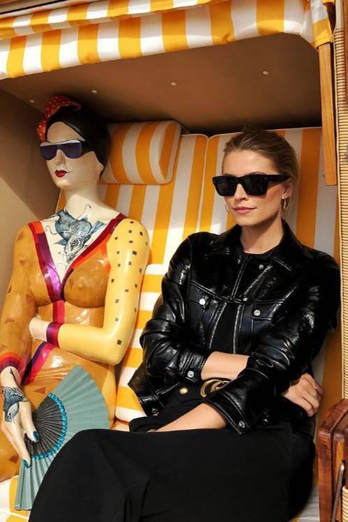 Lack und Leder mal anders: Model Lena Gercke posiert im Strandkorb auf der Aida in schwarzer Lederjacke in Lackoptik.
