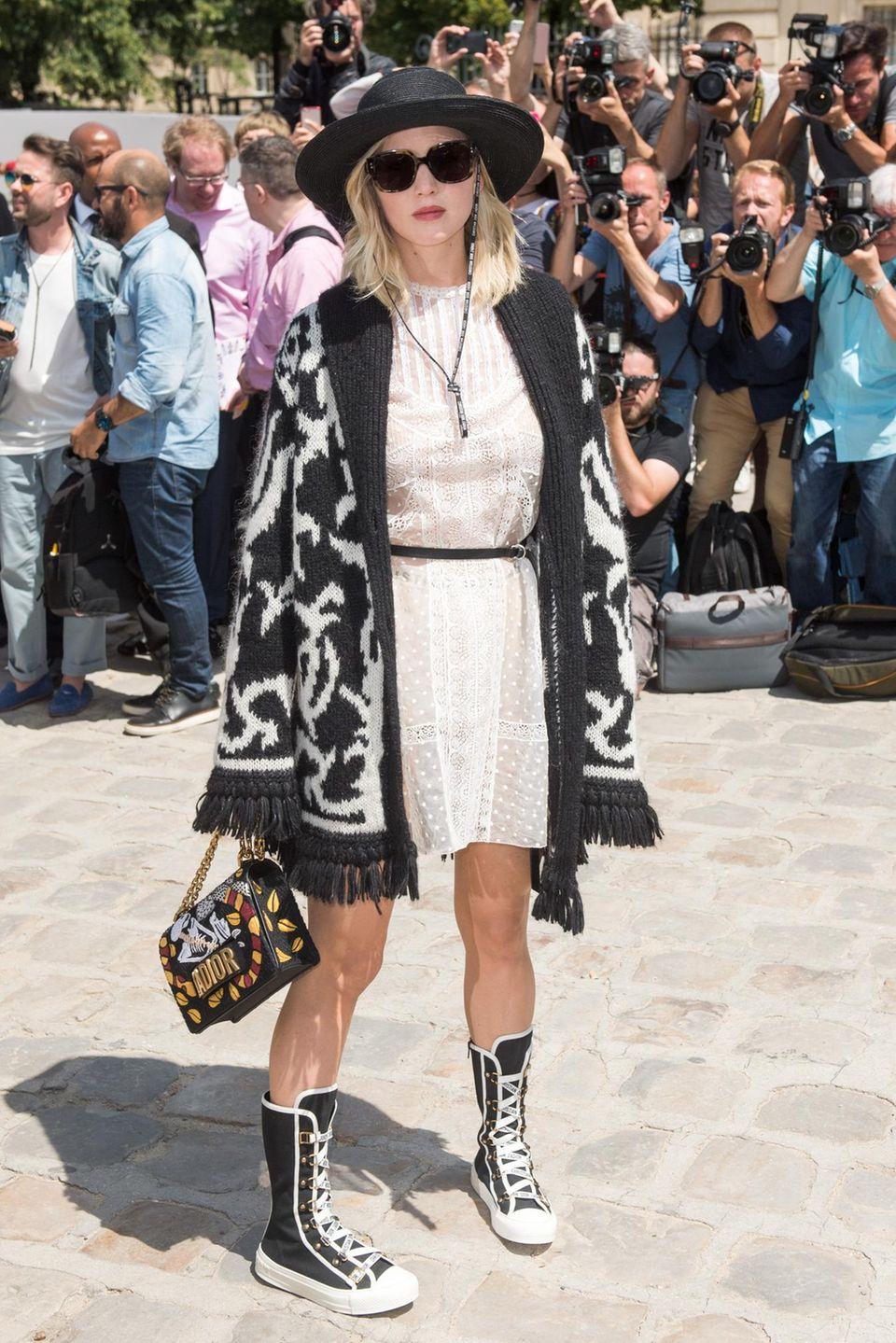 Was war denn da los, J.Law? Jennifer Lawrence präsentiert sich bei Dior mit Boxerstiefel und übergroßer Strickjacke im schwarz-weißen Lotter-Look.