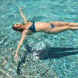Im Partnerlook mit dem Pool schwimmt Model Bar Refaeli auf dem Rücken durchs Wasser und präsentiert dabei ihre kleine, aber feine Babykugel.