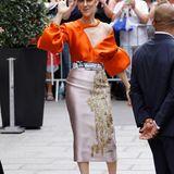 Celine Dion schafft es aktuell Tag für Tag sich mit ihren Looks selbst zu übertreffen. Diese asymmetrische, orangefarbene Bluse mit Oversize-Ärmel lässt sie strahlen und bildet eine harmonische Kombination mit einem roséfarbenen Seidenrock mit goldenen Details.