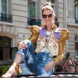 In so einem coolen Look würden wir uns auch von unseren Fans in Paris feiern lassen und kurzerhand mal auf einem Autodach Platz nehmen. Sängerin Celine Dion sieht in diesem extravaganten Blazer einfach nur fabelhaft aus.