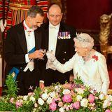 """Wenn ein """"Salud"""" auf ein """"Cheers"""" trifft, kann das nur eines bedeuten: Der spanische König stößt mit der Queen Englands während des Banketts auf einen gelungenen ersten Tag an. Zum Wohl!"""