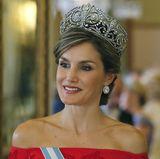 """Königin Letizia, die selten ein Diadem trägt, präsentiert zu diesem besonderen Anlass die """"Fleur de Lys""""-Tiara und Ohrringe von Cartier. Es ist das zweite Mal, dass die spanische Königin dem als """"Diadem der Königin"""" bekannten Schmuckstück die Ehre erweist. Es war einst ein Hochzeitsgeschenk von König Alfonso XIII. an seine Braut Victoria Eugenie und nur Königin Sofia hat die Tiara außerdem vor Letizia getragen."""