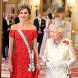 Königin Letizia erscheint zum Staatsbankett in einer roten, bodenlangen Robe von Felipe Varela. Der schmeichelhafte Bardot-Schnitt setzt ihre Schultern toll in Szene. Das Kleid ist mit Blumenstickereien verziert. Dazu kombiniert sie eine rote Clutch von Magrit.