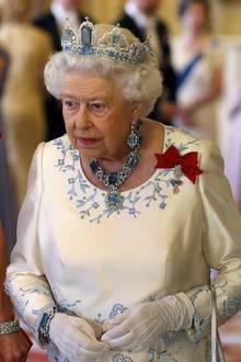 """Queen Elizabeth trägt die """"Brazilian Aquamarine""""-Tiara, die sie 1957 beim Hofjuwelier fertigen ließ. Einige Jahre zuvor, 1953 zu ihrer Krönung, bekam sie vom brasilianischen Volk die Diamant-Halskette mit einem großen, tropfenförmigen Aquamarin und passenden Ohrringen geschenkt."""