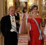 Wer sich von dem funkelnden Schmuckstück nicht allzu sehr ablenken lässt, entdeckt im Hintergrund übrigens Herzogin Catherine und Prinz Harry, die ebenfalls in den Buckingham Palace gekommen sind.