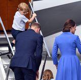 Trotzdem wartet er auf seine kleine Schwester, der von Mama und Papa beim Erklimmen der Stufen geholfen wird.