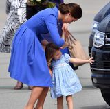 """Wie auch bei ganz """"normalen"""" Familien passt Herzogin Catherine darauf auf, dass nicht nur das Kleidchen sondern auch die Frisur sitzt. Bevor es in den Flieger geht, richtet sie noch einmal das Schleifchen ihrer Tochter, die ganz schnell ihrem Bruder hinterher will."""