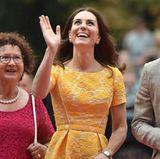 Die Menschen an den Fenstern haben Glück: Herzogin Catherine bemerkt sie sofort und winkt ihnen freudig zu.