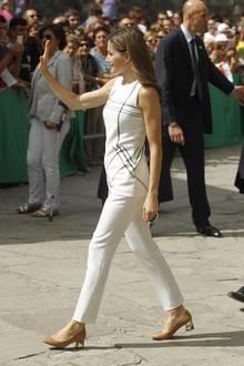 Winkend schreitet Königin Letizia an der wartenden Menge vorbei. Wieder einmal zeigt sie, wie man teure Designerteile mit preiswerteren High-Street-Teilen kombiniert: Zu einem karierten Peplum-Top von Hugo Boss trägt sie eine cremefarbene Hose von Massimo Dutti. Ihre hellbraunen Pumps mit dickem Absatz sind vom spanischen Label Uterque.