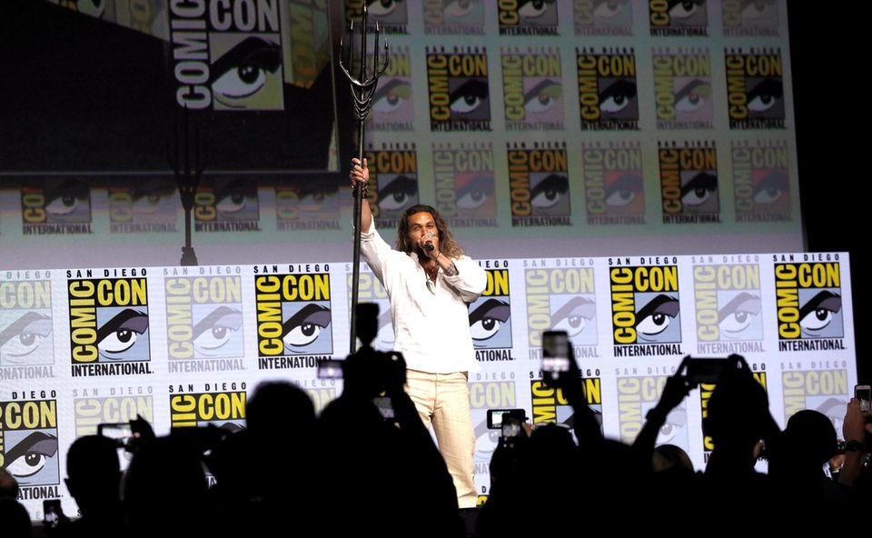 """""""Aquaman"""" Jason Momoa schwingt auf der Bühne seinen Dreizack."""