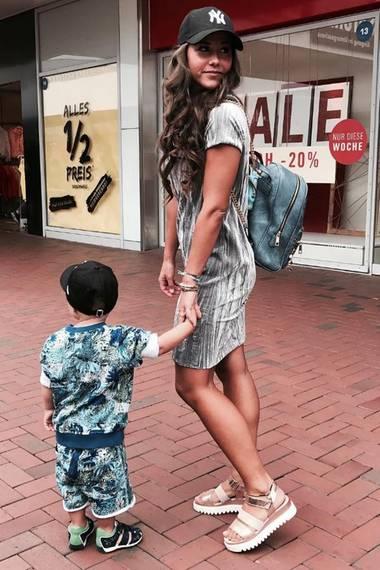 Eine cooler, als der Andere: Sarah und ihr Sohn Alessio präsentieren sich im Partnerlook. Beide tragen eine Cap und wild-gemusterte Outfits. Sarah kombiniert zu ihrem Batik-Kleidchen noch einen Rucksack und Plateau-Sandalen im Metallic Look.