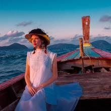 Weiße Bluse mit Stehkragen und Spitzeborten von C&A. Transparentes, knöchellanges Kleid darüber von Wunderkind. Strass-Ohrschmuck von Rada, traditioneller Khmer-Basthut, umwickelt mit Baumwoll-Sarong: Vintage