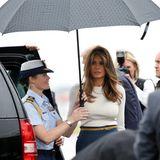 First Lady Melania Trump lässt sich ihren Regenschirm natürlich tragen.