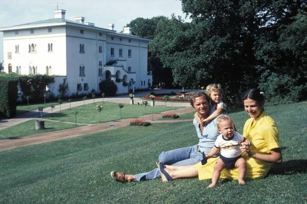 Sommerglück fühlt sich hier zeitlos an: König Carl Gustaf und Königin Silvia im Jahr 1980 mit Victoria (bei Papa) und Carl Philip vor Schloss Solliden