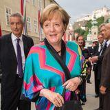"""Bei den Salzburger Festspielen zeigt sich Angela Merkel in diesem Jahr ungewohnt farbenfroh.Für die Premiere von """"Lady Macbeth von Mzensk"""" hat sich die Bundeskanzlerin für diesen auffälligen Seiden-Kimono entschieden, den sie mit schwarzer Hose kombiniert."""