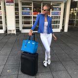 Mit blauer Hermès-Tasche, Koffer von Louis Vuitton und Gucci-Sneaker zum weiß-blauen Outfot reist Victoria bequem und stylisch nach London.