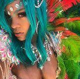Zum mit Juwelen besetzten Bra trägt sie türkisfarbene Haare und aufwendigen Federschmuck.