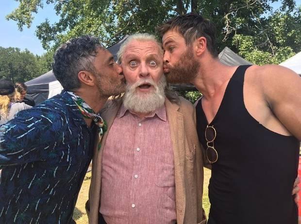 """17. August 2017  """"Thor 3: Ragnarok""""-Regisseur Taika Waititi (li.) und """"Thor""""-Darsteller Chris Hemsworth (li.) haben den Altmeister Anthony Hopkins lieb. Dass es aber gleich zu solch dicken Schmatzern kommt, überrascht den """"Odin""""-Darsteller sichtbar."""