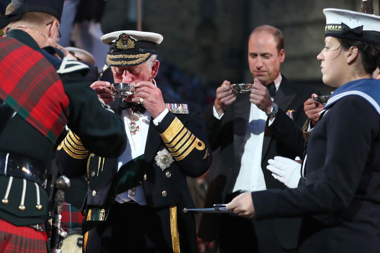Mit von der Partie sind auch Prinz Charles und Prinz William, die beim Empfang alle Traditionen mitmachen. Skeptisch scheint William trotzdem zu bleiben und begutachtet sein Getränk erst einmal, bevor er es schließlich trinkt.
