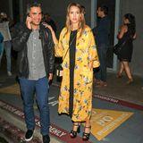 """Die schwangere Jessica Alba besucht im blumig-sommerlichen Mantel-Look die """"Hamilton""""-Premiere in Los Angeles. Die schwarzen Plateau-Heels sind allerdings so hoch, dass sie sich zur Sicherheit doch lieber an Ehemann Cash Warren festhält."""