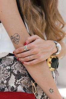 """Auch Lisa Fiege von """"Thelfashion"""" liebt es, gleich mehrere Schmuckstücke an einem Handgelenk zu tragen. Sie kombiniert gleich fünf Ringe von Pandora mit Armreifen und Uhr. Zusammen mit den filigranen Tattoos entsteht ein rockiger Look."""