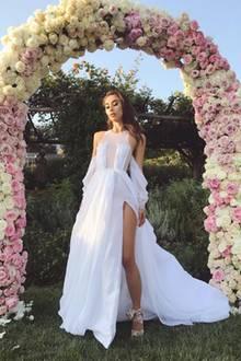 Von vorne ist die Besonderheit des Kleides noch besser zu erkennen: Ein hoher Beinschlitz und durchsichtige Cut-Outs auf der Vorderseite lassen die bodenlange Robe sehr sexy wirken. Dazu sind die Schultern freigelegt. Auf jeden Fall ein sehr außergewöhnliches Brautkleid.