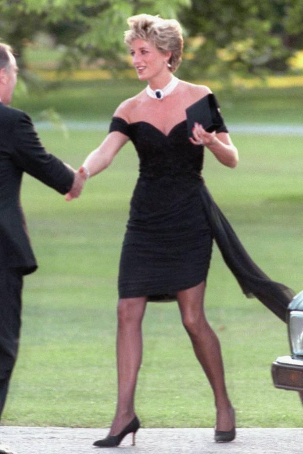 """Prinzessin Diana prägte 1994 den Begriff """"Rachekleid"""", als sie in diesem kleinen Schwarzen von der griechischen Designerin Christina Stambolian beim Empfang der Serpentine Gallery erschien. Was war geschehen? Einen Tag zuvor beichtete Prinz Charles seine Affäre mit Camilla im Fernsehen. Eigentlich eine öffentliche Demütigung für Diana. Diese drehte den Spieß so jedoch um. Plötzlich schrieben alle über ihren heißen Auftritt, nicht aber über Charles."""