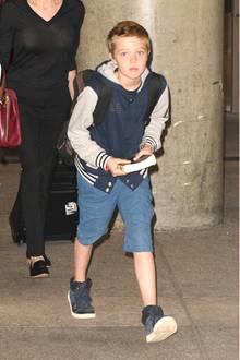 """Zwei Jahre vorher heißt es bei Shiloh Jolie-Pitt """"College statt Camouflage"""". Da trägt sie auf Reisen meist nämlich ihre Jacke im Schul-Look. Der Dreiviertelhose ist sie aber auch in 2015 schon treu."""