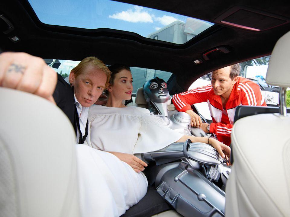 Trip zu viert: Maria kann mehr als nur dekorativ herumliegen. Zum Beispiel als Armpolster dienen, wie hier für Anna Bederke. Flankiert wird Anna in der BMW-Limousine von Ben Becker und Trystan Pütter.
