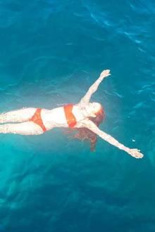 Model Barbara Meier lässt sich in einem farblich auf ihre roten Haare abgestimmten Bikini auf dem blauen Meer treiben - ein unglaublich schöner Kontrast.