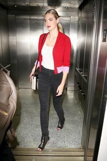 ... Den Flug hat das Model für einen Garderobenwechsel genutzt und den Pulli durch ein schlichtes Top und ein roten Cardigan ersetzt. Auch die Nägel hat sich Kate Upton noch schnell lackiert.