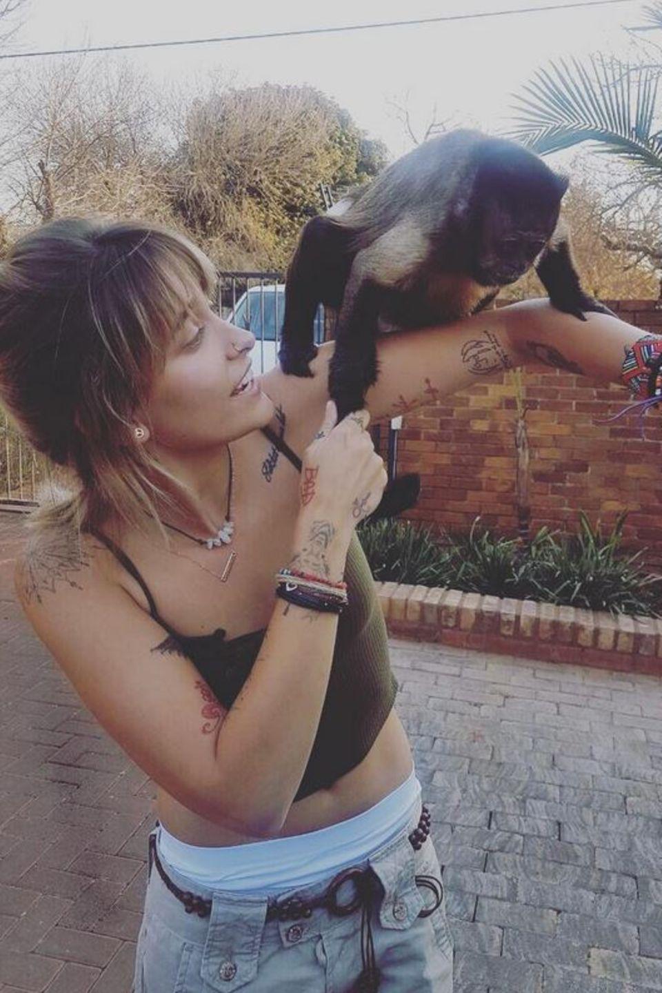 Ich glaub mich laust ein Affe: Paris Jackson freut sich über ihren tierischen Begleiter, der neugierig auf sie zukommt.