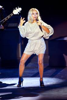 """Beim großen """"Sommer-Hit-Festival 2017"""" in Timmendorfer Strand trägt Michelle einen gold schimmernden Einteiler. Durch die extrem weiten Fledermausärmel wirkt der kurze Overall etwas groß geraten."""