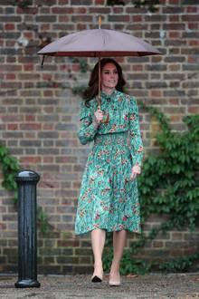 Am Abend vor dem 20. Todestag ihrer Schwiegermutter, Prinzessin Diana von Wales, besucht Herzogin Catherine zusammen mit Prinz William und Prinz Harry den Gedächtnisgarten des Kensington Palasts. Das sommerliche Seidenkleid mit floralem Muster von Prada für 1420 Euro und nudefarbene Pumps. Ihren Look schützt sie stilecht mit einem braunen Regenschirm.