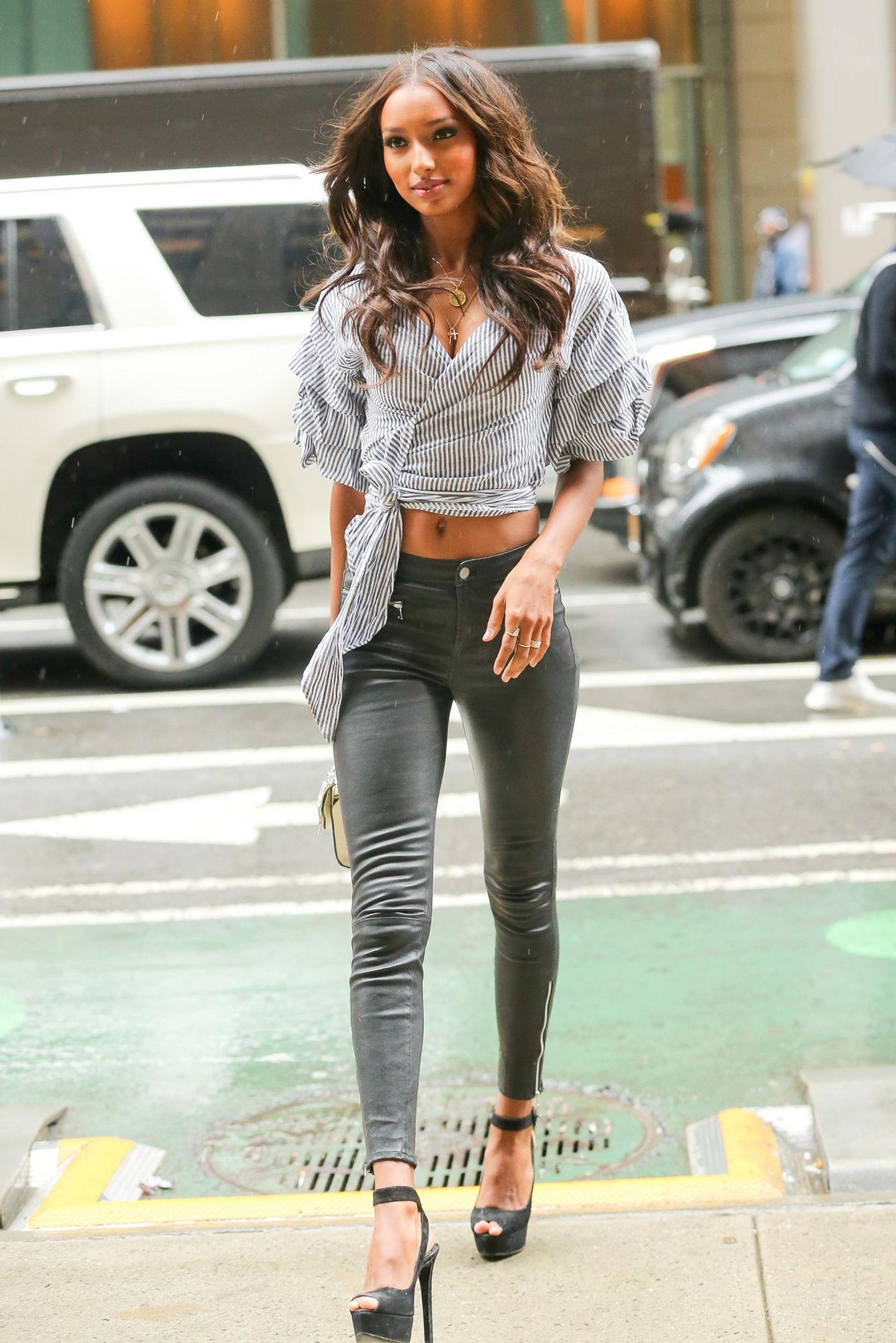 """Jasmine Tookes setzt mit einer skinny Jeans und Plateau-Heels ihre endlos langen Beine in Szene. Dazu kombiniert sie eine gestreifte Wickelbluse und trägt die Haare in """"Victoria's Secret""""-typischen Beachwaves."""