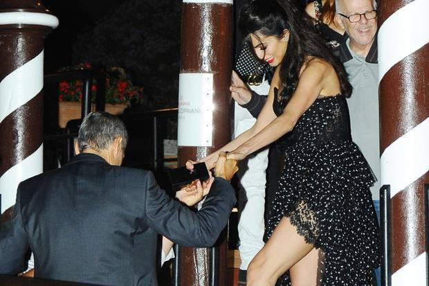 Liebevoll bietet George Clooney seiner strahlenden Frau Amal eine helfende Hand beim Besteigen eines Wassertaxis. Der große Schritt gibt den Blick auf die Spitzendetails ihres Luxuskleids frei.