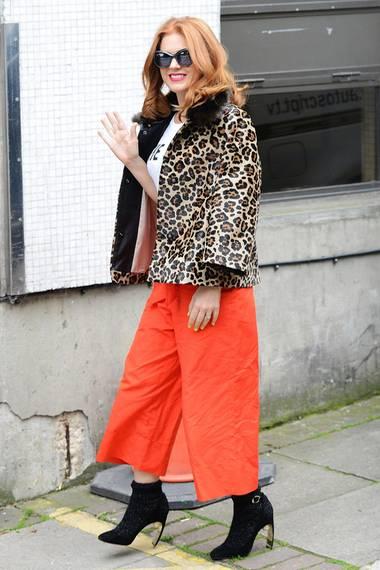 """Hingucker-Mix! Isla Fisher kombiniert ihre stylische Leo-Print Jacke mit knalliger, orangefarbener Culotte und schwarzen """"Lola""""-High-Heels von Nicolas Kirkwood."""