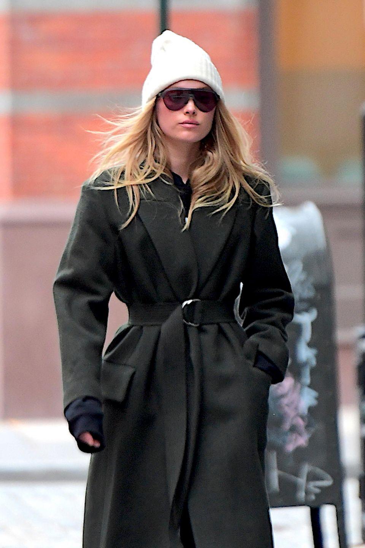 Topmodel Elsa Hosk schwebt im übergroßen Mantel und weißer Strickmütze über die Straßen von New York.