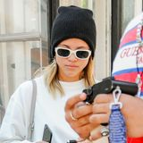 Schwarze Strickmütze, weißes Sweatshirt, dazu die passende Sonnenbrille, und fertig ist Sofia Richies Lässig-Look.
