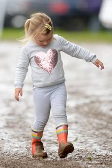 Ein Herz für Matsch und Pfützen hat Zara Phillips süße Tochter Mia Tindall, die auf Festivals und bei Pferderennen nie eine Chance auslässt, durch den Schlamm zu stapfen. Damit ihr hellgraues Ensemble dabei nicht dreckig wird, hat ihre royale Mama ihr kunterbunte Gummistiefel angezogen.