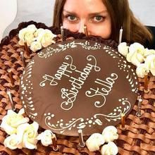 Stella McCartney versteckt sich hinter ihrer riesigen Schokoladen-Geburtstagstorte.